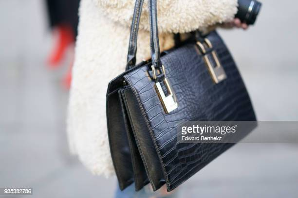 Guest wears a black crocodile leather bag, during London Fashion Week February 2018 on February 16, 2018 in London, England.