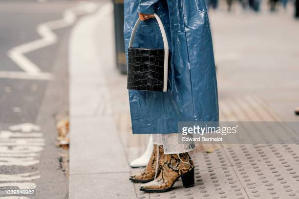 Guest wears a black crocodile leather bag, snake print leather boots, during London Fashion Week September 2018 on September 18, 2018 in London,...
