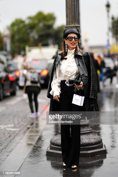 A guest wears a black crocodile pattern Chanel hat Chanel mirrored sunglasses Chanel earrings a creamcolor shirt with ruffled cuffs and a bib...