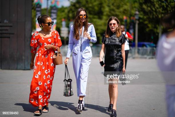 A guest wears a black dress a guest wears a blue outfit a guets wears a red dress with flower prints outside Chanel during Paris Fashion Week Haute...