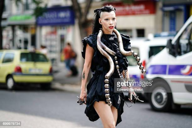 A guest wears a black dress a necklace representing snake with balls made of metal and black heels outside the Y/Project show during Paris Fashion...