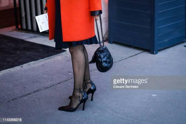 A guest wears a black dress an orange coat a black quilted bag black fishnet tights black heeled pointy pumps on April 12 2019 in Paris France