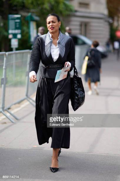 Guest wears a black dress, black cropped large pants, black shoes, outside Issey Miyake, during Paris Fashion Week Womenswear Spring/Summer 2018, on...