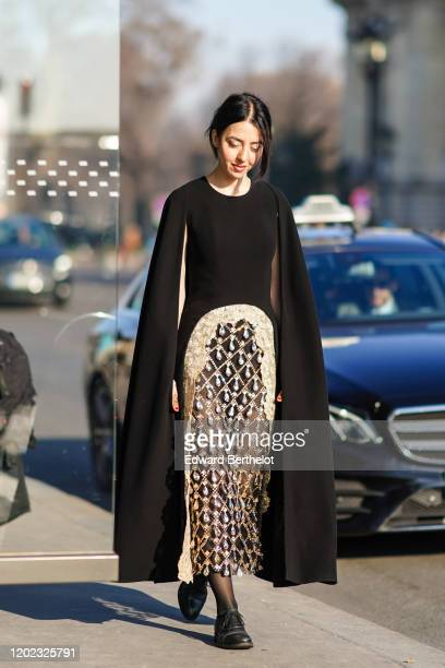 Guest wears a black dress with a cape and a bejeweled part, outside Elie Saab, during Paris Fashion Week - Haute Couture Spring/Summer 2020, on...