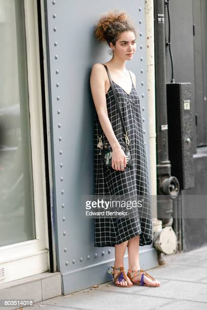 Guest wears a black dress with a white printed grid, and colorful sandals, and has curly hair, outside the Dries Van Noten show, during Paris Fashion...