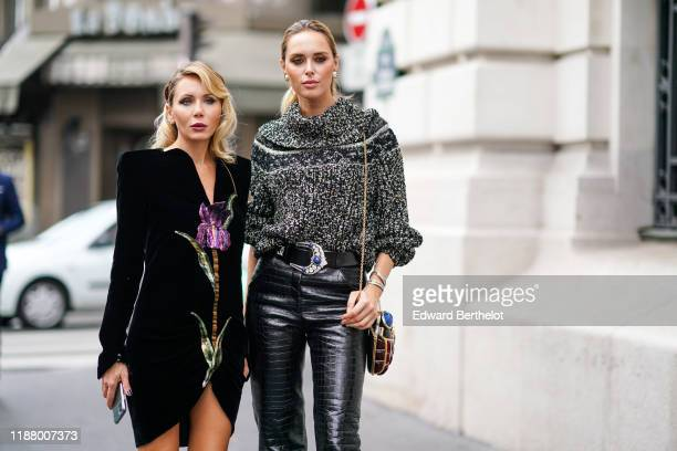 A guest wears a black dress with floral print black leather high shoes a guest wears a wool pullover a belt black leather crocodile pattern pants...