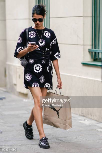 A guest wears a black dress with white prints a puma paper bag black sneakers sunglasses outside the Dries Van Noten show during Paris Fashion Week...