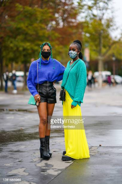 Guest wears a black face mask, a blue oversized wool pullover, black leather shorts, a green bag ; a guest wears a colored floral print face mask, a...