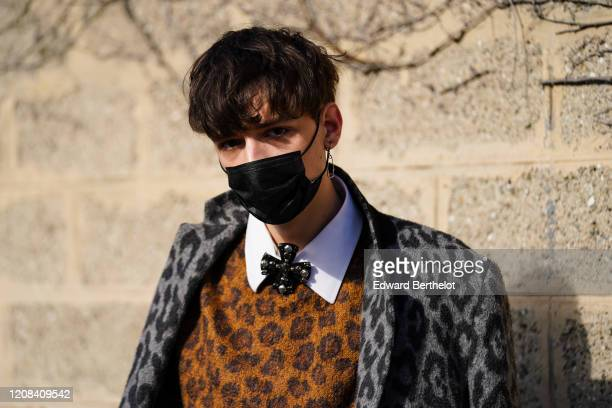 A guest wears a black face mask a gray leopard print coat a brown wool leopard print pullover a white shirt outside BOSS during Milan Fashion Week...