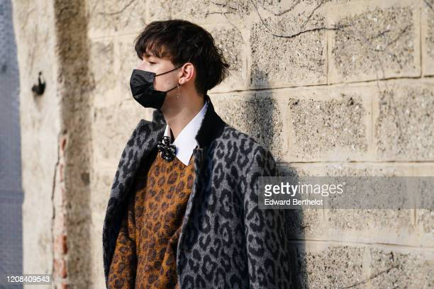 Guest wears a black face mask, a gray leopard print coat, a brown wool leopard print pullover, a white shirt, outside BOSS, during Milan Fashion Week...