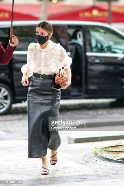 A guest wears a black face mask a white ruffled mesh lace shirt a belt a black leather skirt a leather Miu Miu bag shoes outside Miu Miu during Paris...