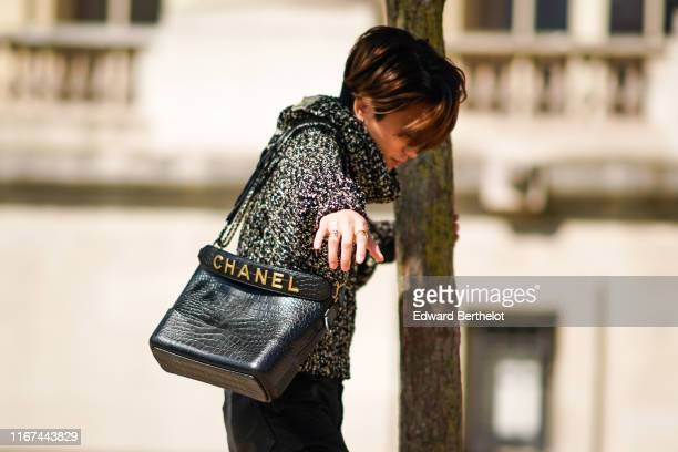 A guest wears a black flecked sweater a black Chanel alligator pattern bag outside the Chanel Cruise Collection 2020 At Grand Palais on May 03 2019...