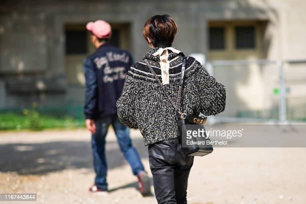 A guest wears a black flecked sweater black leather pants a Chanel alligator pattern black bag outside the Chanel Cruise Collection 2020 At Grand...
