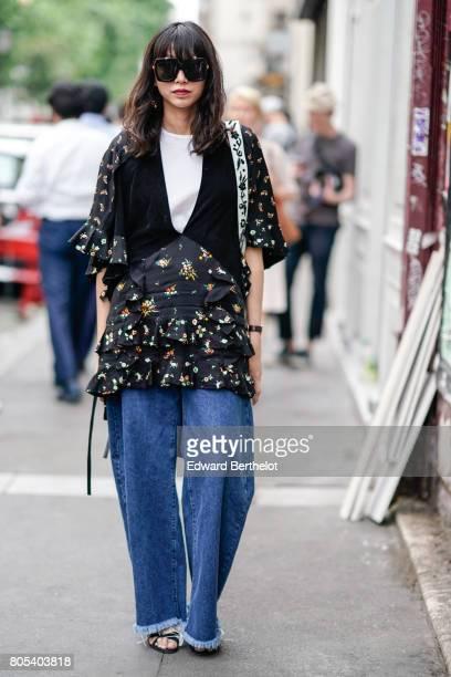 A guest wears a black floral print dress a white top blue oversized large denim jeans pants sunglasses after Yohji Yamamoto show during Paris Fashion...