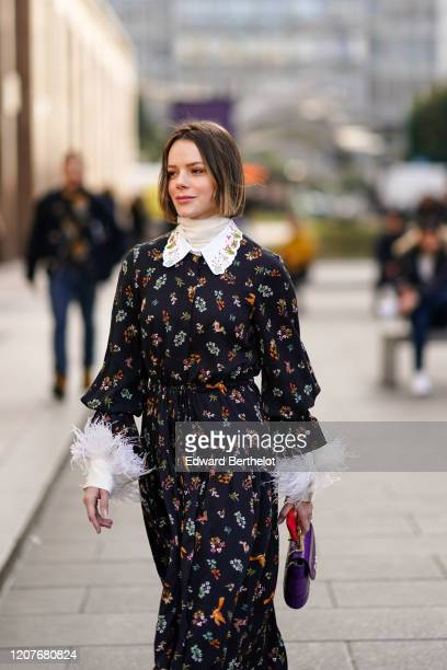 Guest wears a black floral print dress with fluffy parts, a turtleneck top, a purple Chloe bag, outside Vivetta, during Milan Fashion Week...