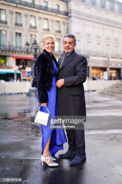 A guest wears a black fluffy jacket a purple long dress a white handbag white strappy pumps A guest wears a geometric design scarf a thin stripes...