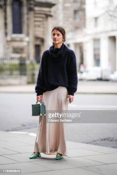 A guest wears a black fluffy turtleneck a flowing beige skirt a green handbag green pumps during London Fashion Week February 2019 on February 19...