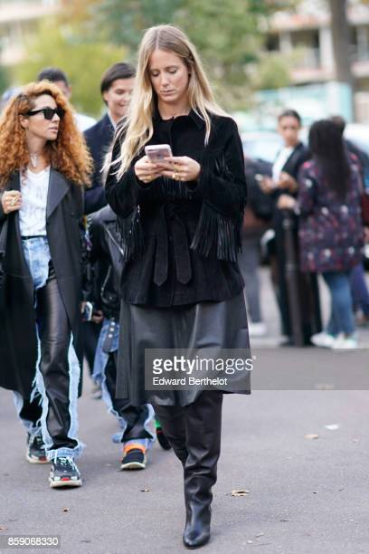 A guest wears a black fringed coat a black skirt black leather boots outside CDG Comme des Garcons during Paris Fashion Week Womenswear Spring/Summer...