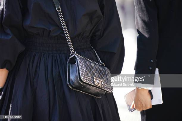 A guest wears a black gathered and flowing dress a black Chanel studded bag outside the Chanel Cruise Collection 2020 At Grand Palais on May 03 2019...