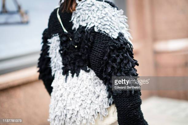 A guest wears a black grey and white roughly knit sweater during London Fashion Week February 2019 on February 16 2019 in London England
