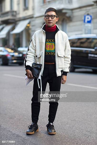A guest wears a black Gucci sweatshirt and black Loewe pouch during Milan Men's Fashion Week Fall/Winter 2017/18 on January 15 2017 in Milan Italy