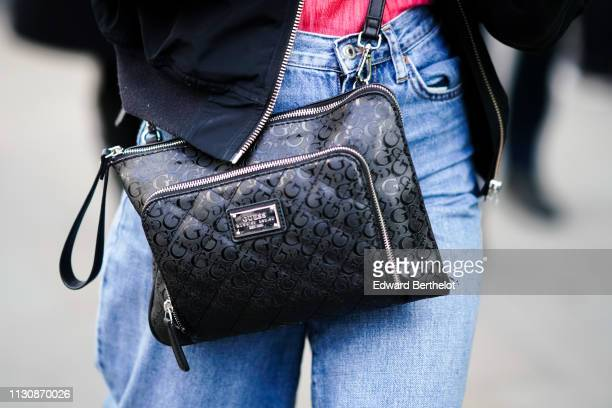 A guest wears a black Guess bag during London Fashion Week February 2019 on February 19 2019 in London England