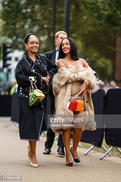 Guest wears a black hair band, earrings, a necklace, a black studded trench coat, a glittering iridescent green bag, yellow floral print pointy pumps...