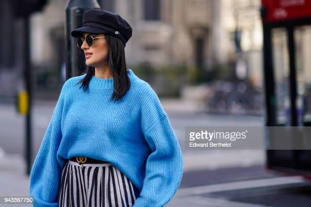 A guest wears a black hat a blue wool pull over a Gucci belt a black and white striped skirt during London Fashion Week February 2018 on February 16...