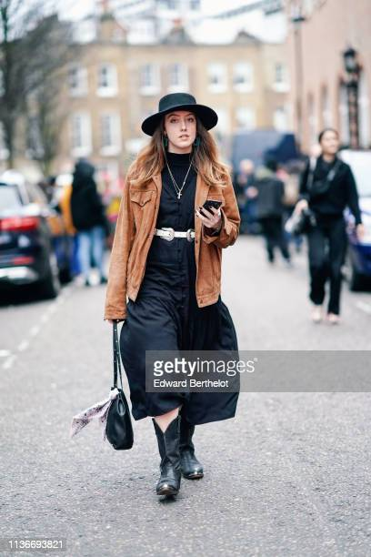 A guest wears a black hat a tan color suede jacket a black dress with puff divided skirt a white belt a black bag black metallic end cowboy boots...
