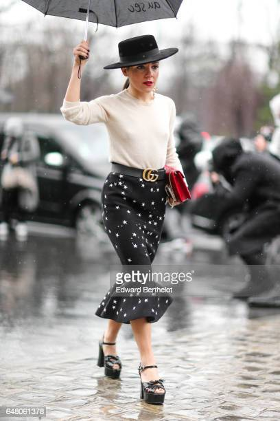2481a5f3 A guest wears a black hat a white pull over a Gucci belt a black skirt