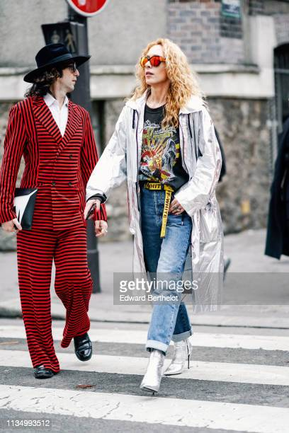 A guest wears a black hat a white shirt a red and black striped doublebreasted suit black shoes a back and white bag Elina Halimi wears sunglasses a...