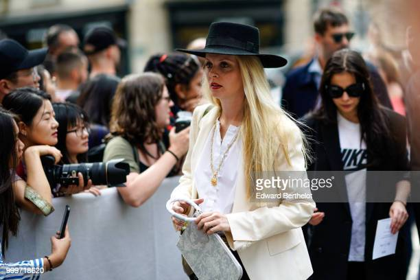 A guest wears a black hat and a white blazer jacket outside Dior during Paris Fashion Week Menswear SpringSummer 2019 on June 23 2018 in Paris France