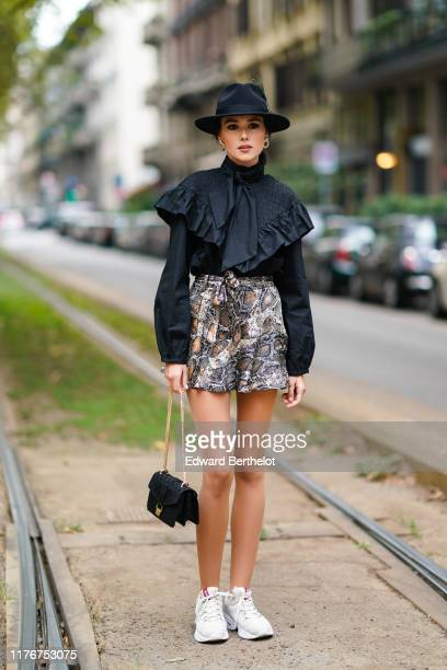 A guest wears a black hat earrings a black hineck top with a ruffled smocked bib and a lavaliere grey and light brown python pattern flowing mini...