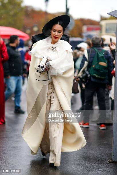 Guest wears a black hat, earrings, a Chanel brooch, a white scarf, a cream-color long cape, assorted pants, a black and white bag, outside Chanel,...