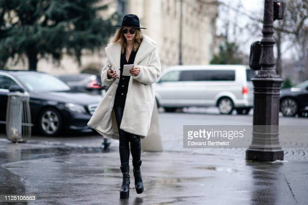 A guest wears a black hat sunglasses a white coat black leggings black leather shoes outside Alexandre Vauthier during Paris Fashion Week Haute...