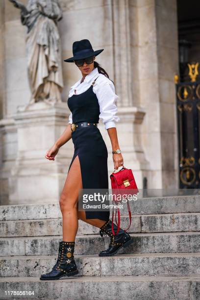 Guest wears a black hat, sunglasses, a white shirt, a pinafore navy blue side-slit dress, a red Gucci bag, black studded lace-up boots, a studded...