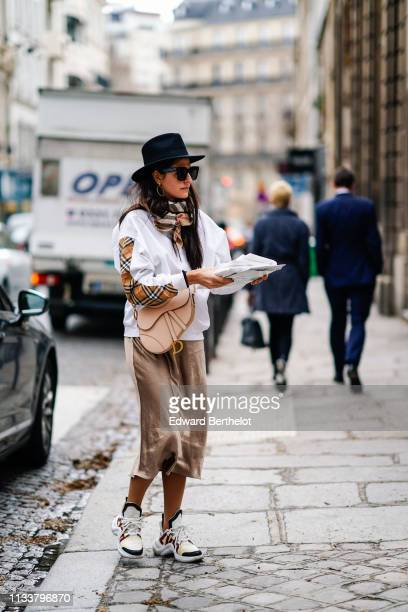 A guest wears a black hat sunglasses earrings a camel brown and white scarf a white top a beige Dior bag a lustrous beige skirt Louis Vuitton...