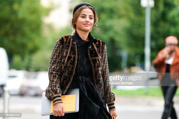 Guest wears a black head band, a black mini dress, a brown Fendi fluffy jacket, outside the Fendi show during Milan Fashion Week Spring/Summer 2020...