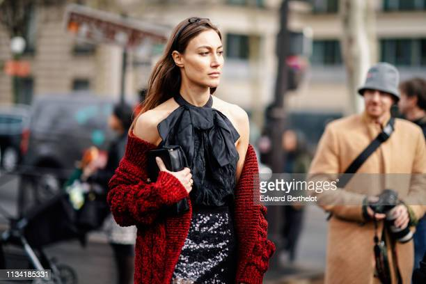 A guest wears a black headband a black halter top a red knit coat a glittering sequined grey skirt outside Miu Miu during Paris Fashion Week...