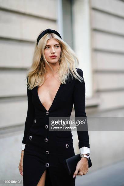 Guest wears a black headband, a black low neck dress with buttons, a clutch, outside Alessandra Rich, during Paris Fashion Week - Womenswear Spring...