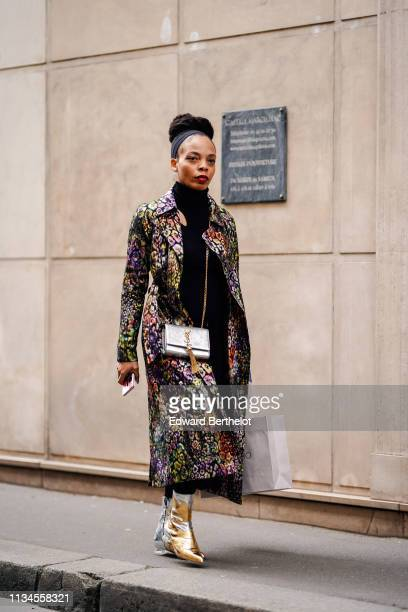 Guest wears a black headband, a black turtleneck, a multicolor floral print black coat, a shiny silver YSL bag, shiny silver pointy boots with golden...