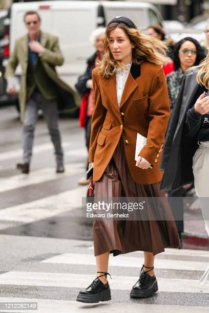 Guest wears a black headband, a white top with a frilly hi-neck, a brown leather pleated skirt, a rust-color jacket with brass buttons, black...
