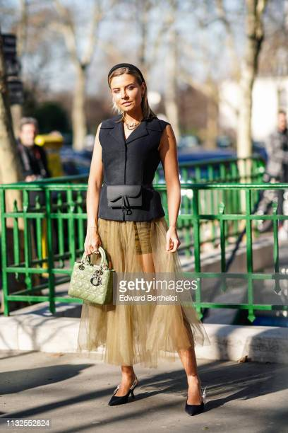 A guest wears a black headband necklaces a black sleeveless vest a black Dior beltbag a transparent yellow pleated tulle skirt an almondgreen Lady...