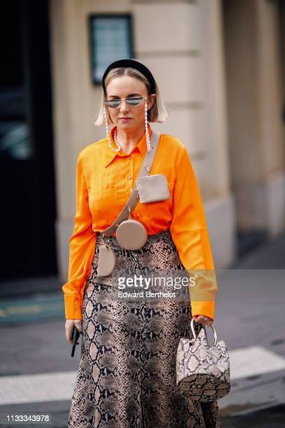 A guest wears a black headband sunglasses a beige crossbody strap with three small bags an orange shirt a beige python pattern long skirt a beige...