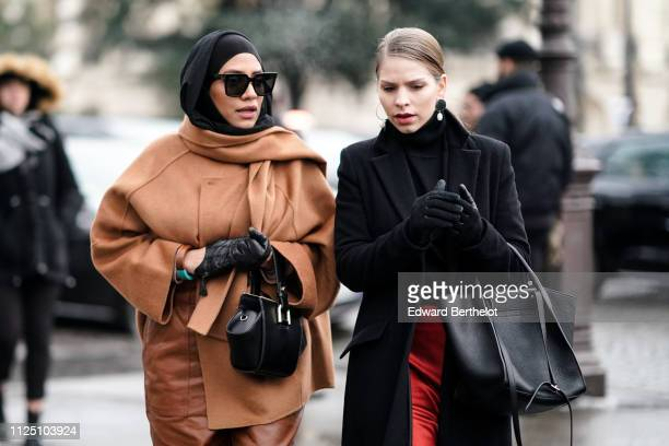 A guest wears a black hijab a brown coat a nag and black leather gloves a guest wears earrings a black coat red pants gloves outside Alexandre...