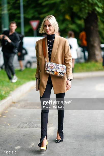 A guest wears a black hineck Fendi top with white Fendi logo pattern a camel oversized jacket a Fendi colorful beadwork bag skinny black pants with...