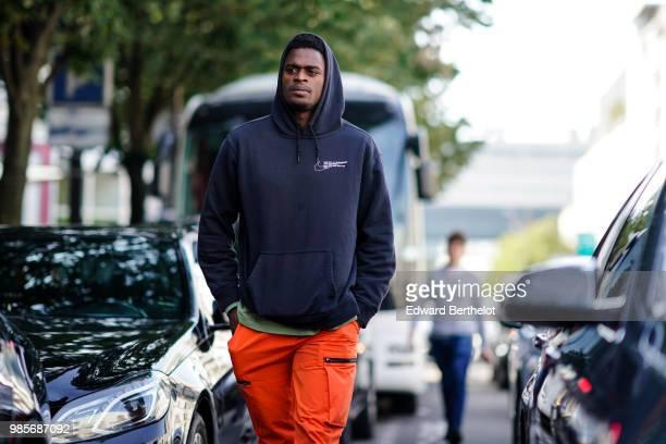 A guest wears a black hoodie sweater orange pants outside 1017 ALYX 9SM during Paris Fashion Week Menswear SpringSummer 2019 on June 24 2018 in Paris...