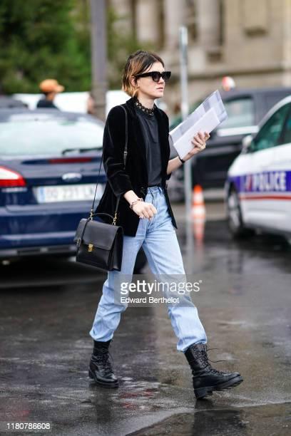 A guest wears a black jacket a black leather bag pale blue denim pants black leather boots a tshirt necklace sunglasses outside Chanel during Paris...