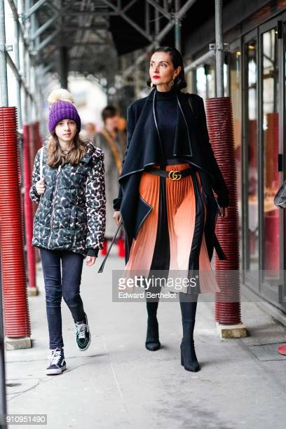 A guest wears a black jacket a black top a Gucci belt an orange pleated skirt black boots outside Alexis Mabille during Paris Fashion Week Haute...