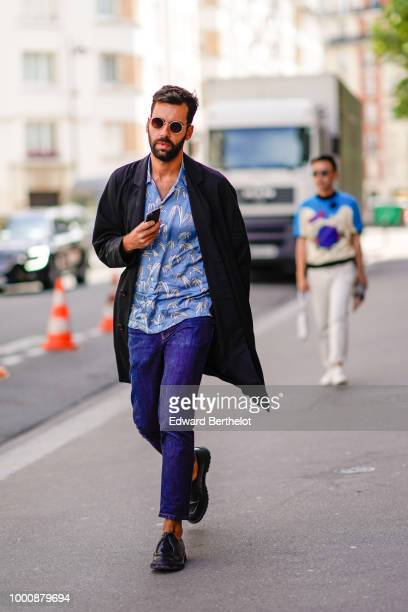 A guest wears a black jacket a blue shirt blue cropped pants black shoes outside Wooyoungmi during Paris Fashion Week Menswear SpringSummer 2019 on...